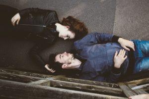 寝転んで向き合うカップル